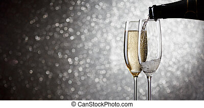 Photo of bottle with pouring wine in wine glasses on gray background