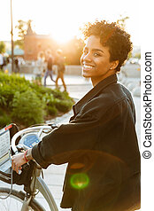 Photo of brunette african american woman looking at camera while sitting on bicycle in city park