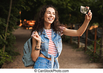 Photo of brunette pretty woman 18-20 with backpack, laughing and taking selfie photo on smartphone while walking along path in green park