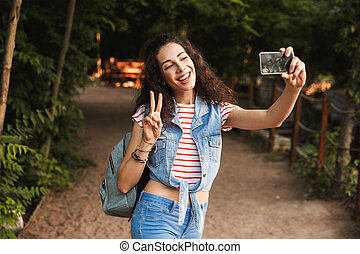 Photo of brunette pretty woman 18-20 with backpack, showing peace sign and taking selfie on smartphone while standing on path in green park