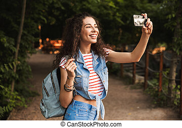 Photo of brunette pretty woman 18-20 with backpack, smiling broadly and taking selfie photo on cell phone while walking along path in green park