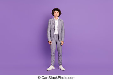 Photo of calm concentrated confident pupil schoolboy guy posing wear grey suit isolated violet color background
