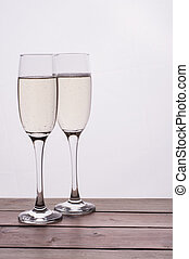 Champagne glass on wooden table against white background