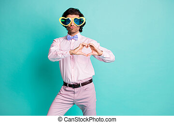 Photo of charming brunet wavy hair gentleman dressed pink shirt blowing kiss showing heart arms fingers isolated turquoise color background