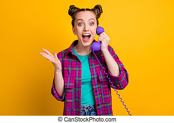 Photo of charming crazy funky lady two funny buns hold cable telephone, handset speak friends listen fresh gossips rumors chatterbox wear casual plaid shirt isolated yellow color background