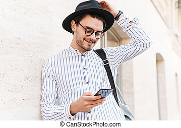 Photo of cheerful caucasian man typing on cellphone and smiling while leaning on wall in city street