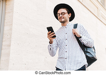 Photo of cheerful caucasian man typing on cellphone and smiling while walking in city street