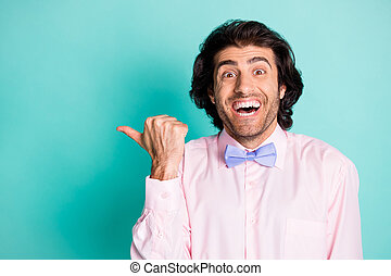 Photo of cheerful curly man wear pink outfit pointing thumb finger empty space isolated turquoise color background