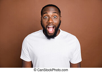 Photo of cheerful handsome attractive funny black man with bristle shocked about sales started expessing positive emotions on face isolated pastel brown color background