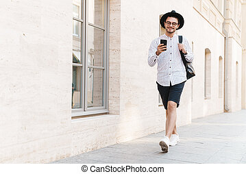Photo of cheerful handsome man typing on cellphone and smiling while walking in city street