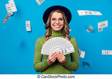 Photo of cheerful lady hold fan dollar bucks rich person freelance salary successful business woman money falling from sky wear specs hat green turtleneck isolated blue color background
