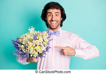 Photo of cheerful positive curly wavy hair fiance wear pink outfit pointing bunch flowers isolated turquoise color background