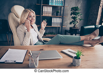 Photo of cheerful positive entrepreneur having finished working on her project and affording to speak by phone with legs on table