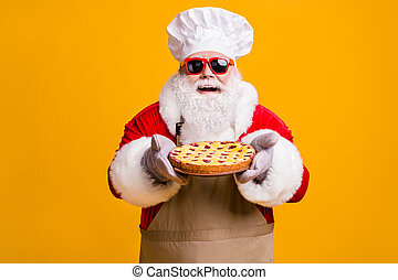 Photo of cheerful santa claus chef headwear grandpa grey beard hold fresh sweet big pie jam filler wear red x-mas costume gloves sun specs cap apron isolated yellow color background