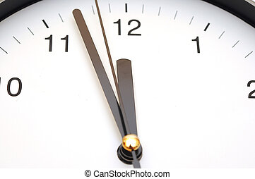 Photo of clock showing five minutes to noon