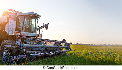 Photo of combine harvester working in field during day