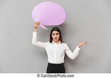 Photo of concerned woman in white shirt and black skirt throwing hand aside while holding copyspace bubble for text, isolated over gray background