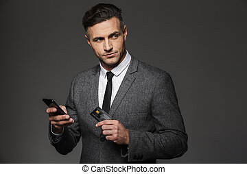 Photo of confident successful man in suit and tie holding cell phone and credit card, isolated over gray background