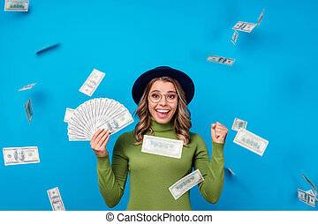 Photo of crazy emotional lady hold fan dollar bucks freelance salary successful business woman catch money falling from sky wear specs hat green turtleneck isolated blue color background