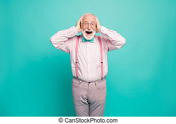Photo of crazy grandpa positive expression arms on head good mood addicted shopper wear specs pink shirt suspenders bow tie pants isolated bright teal color background