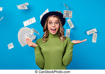 Photo of crazy lady hold fan dollar bucks rich freelance salary successful business woman catch money falling from sky wear specs hat green turtleneck isolated blue color background