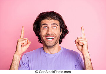 Photo of crazy young guy indicate fingers up empty space wear violet shirt isolated pastel pink color background