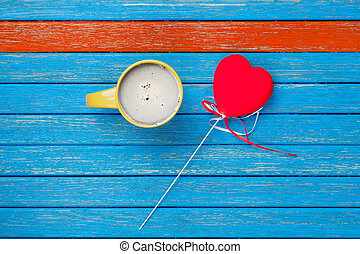 photo of cup of coffee and heart shaped toy on the wonderful wooden background in pop art style