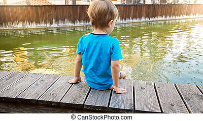 Photo of cute 3 years old little boy sitting on the riverebank at water canal in old town and splashing water with feet.
