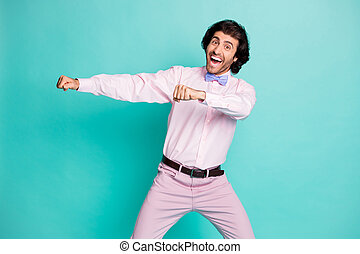 Photo of cute brunet wavy hair disco man dressed pink outfit dancing stretching fists side isolated turquoise color background
