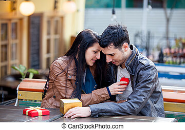 photo of cute couple sitting on the bench and holding heart shaped toy on the wonderful cafe background