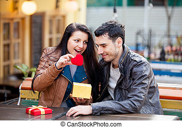 photo of cute couple sitting on the bench and looking at the heart shaped toy on the wonderful cafe background