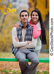 photo of cute couple sitting on the bench on the wonderful autumn trees background