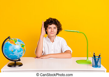 Photo of cute funny school boy wear white shirt smiling siting desk rising arm isolated yellow color background