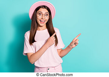 Photo of cute girl dressed pink t-shirt retro cap pointing two fingers empty space open mouth isolated teal color background