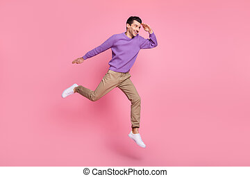 Photo of cute sweet young guy wear violet sweater jumping high looking far away empty space isolated pink color background
