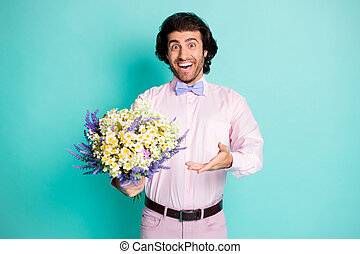 Photo of cute toothy curly hair man wear pink outfit presenting you bunch fresh flowers romantic date isolated teal color background
