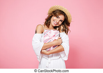 Photo of cute young brunette with charming smile, hugging gift box, looking at camera