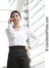 Photo of cute young business woman talking on her smartphone, Serious