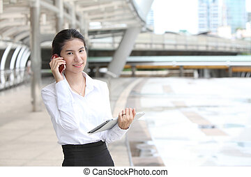 Photo of cute young business woman talking on her smartphone, Smile