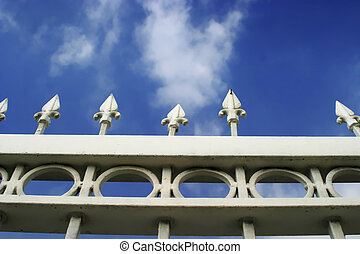 Photo of detail of white metal gate with blue sky