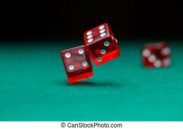 Photo of dice falling on green table in casino