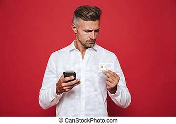 Photo of european man in white shirt holding credit card and smartphone, isolated over red background