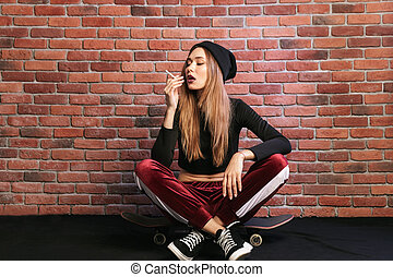 Photo of european sporty girl 20s, sitting on skateboard with cigarette, against brick wall