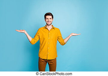 Photo of excited cheerful handsome guy presenting you two sides of project to find plus minus wearing formally smiling toothily isolated over blue pastel color background