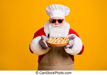 Photo of excited dreamy santa chef headwear grandpa grey white beard hold fresh sweet pie jam yummy flavor wear x-mas costume gloves sun specs cap apron isolated yellow color background