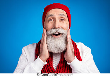 Photo of excited positive person arms on cheeks near open mouth speak isolated on blue color background