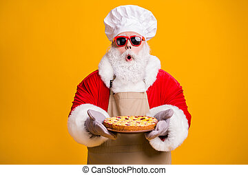Photo of excited santa claus chef headwear grandpa grey beard hold ready fresh sweet big pie jam masterpiece wear x-mas costume gloves sun specs cap apron isolated yellow color background
