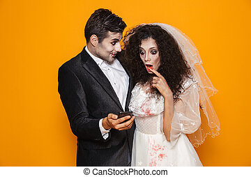 Photo of excited zombie couple bridegroom and bride wearing wedding outfit and halloween makeup using smartphone, isolated over yellow background