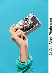 Photo of female hand with telephone on empty pink background