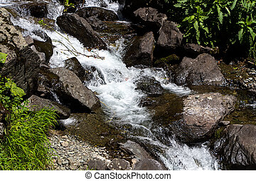 Photo of flowing water among  dark stones
